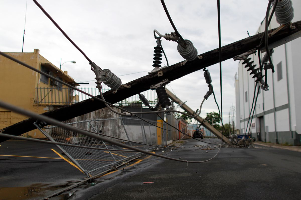 Power line poles downed by the passing of Hurricane Maria lie on a street in San Juan, Puerto Rico on November 7, 2017.