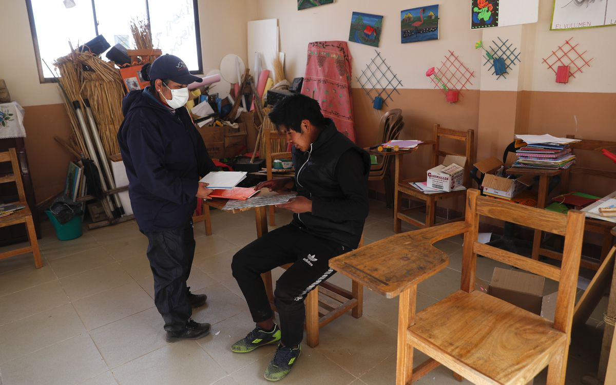 Instructor Marina Vasquez and student Jose Choque go over his homework at the school in the Urus del Lago Poopo indigenous community. Aided by the government and a foundation, community elders have invited teachers from a related branch of the Uru to teach their native tongue to their children.