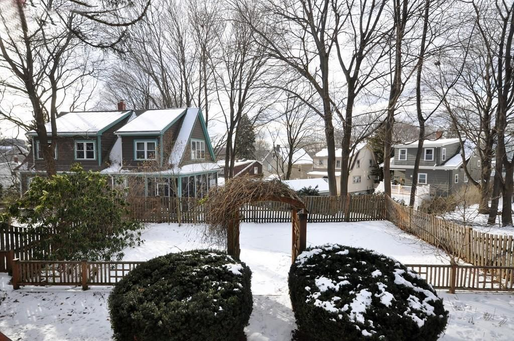 The view of a fenced-in, snow-covered square backyard from a house.