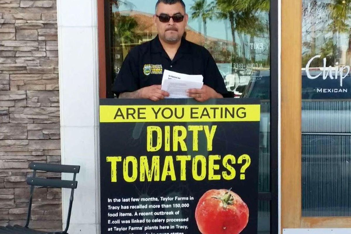 A man protests Taylor Farms' treatment of workers at a California Chipotle
