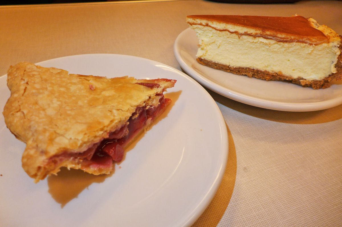 A piece of cherry pie next to a wedge of cheesecake.