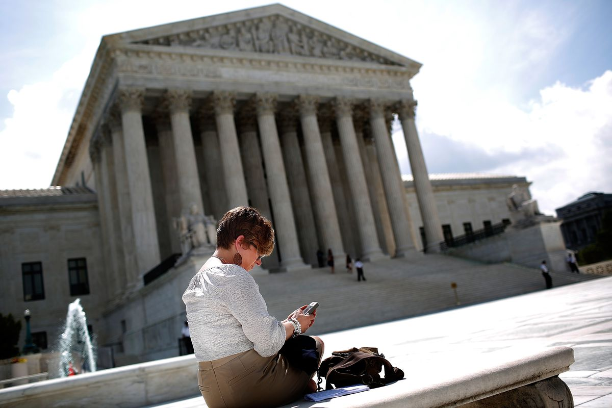 An affluent-looking white lady using a cellphone in front of the Supreme Court.