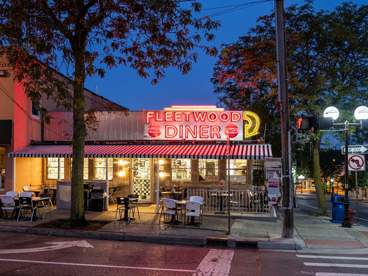 A diner on a corner with a striped awning and a red and yellow neon sign shown at dusk.