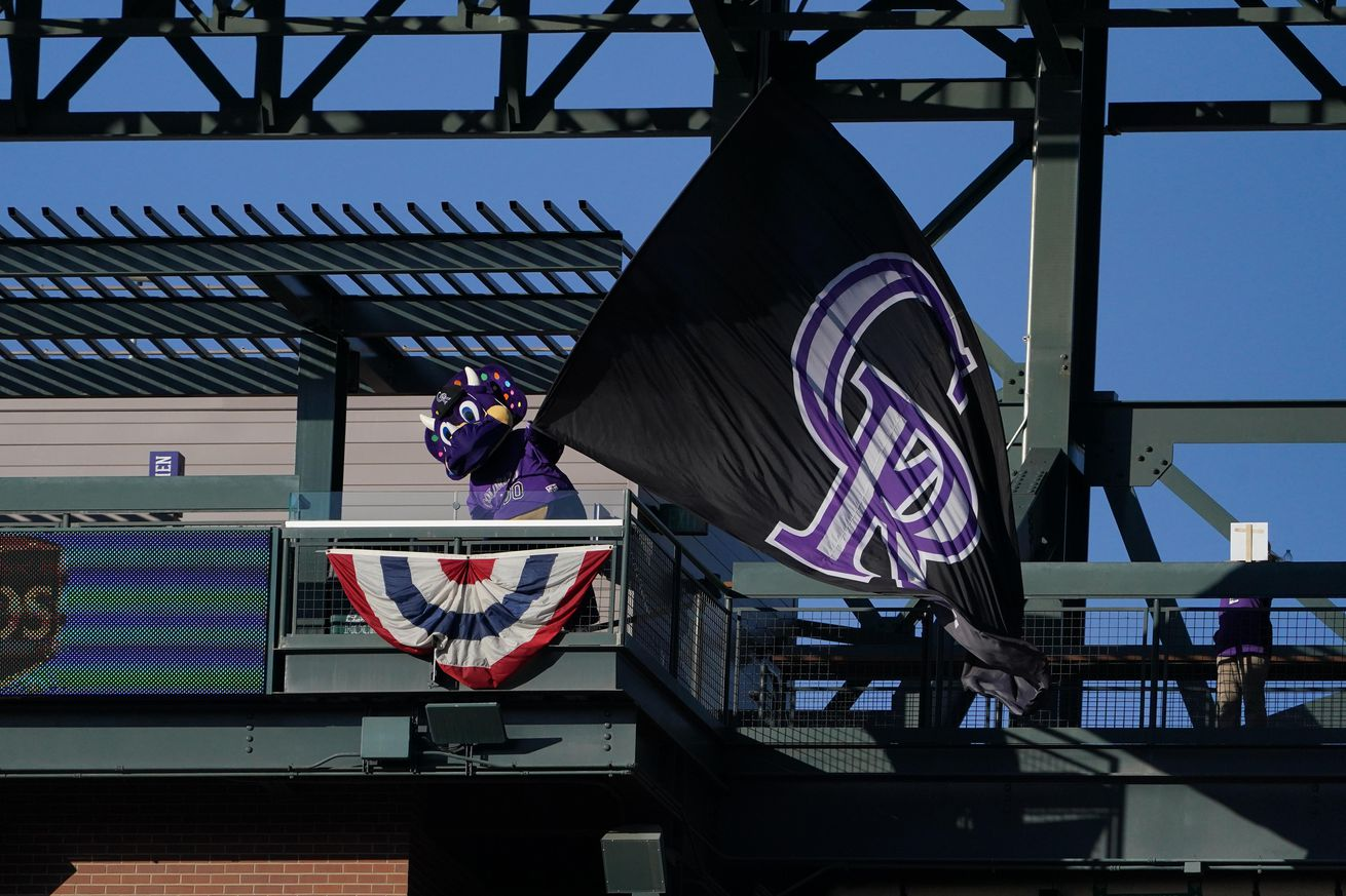 Colorado Rockies mascot Dinger performs by waving a giant CR flag before a game against the Los Angeles Dodgers at Coors Field.