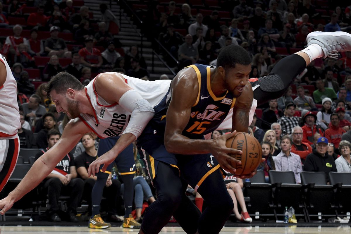 Portland Trail Blazers center Jusuf Nurkic goes flying as he goes up to defend against Utah Jazz forward Derrick Favors during the second half of an NBA basketball preseason game in Portland, Ore., Sunday, Oct. 7, 2018. Utah won, 123-112. (AP Photo/Steve