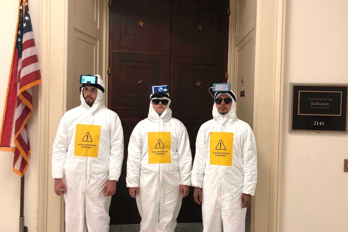 Dressed in hazmat-like jumpsuits, wearing smartphones strapped to their heads, activists descend upon Congress to protest facial recognition.