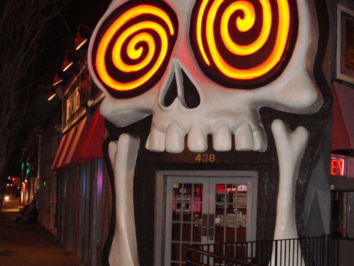 Doorway surrounded by skull and swirly eyes.