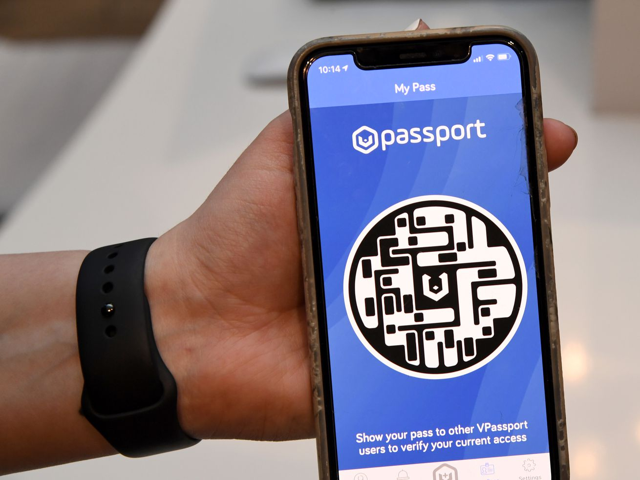 An employee demonstrates the HELIIX Health Passport at The Cosmopolitan of Las Vegas earlier this month. Such vaccine passports won't be required in Illinois, Gov. J.B. Pritzker said Friday.