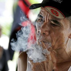 An Indonesian man smokes a cigarette in Jakarta, Indonesia, Tuesday, Sept. 11, 2012. Indonesian men rank as the world's top smokers, with two out of three of them lighting up in a country where cigarettes cost pennies and tobacco advertising is everywhere.