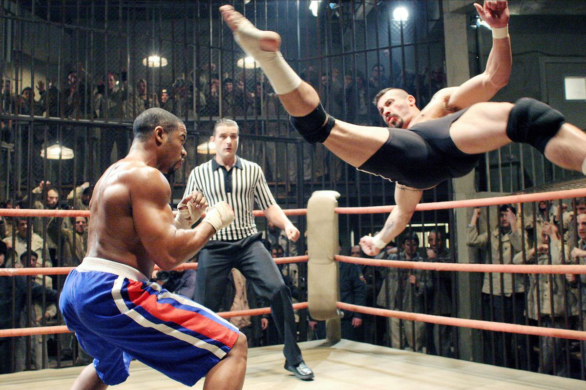 Actor Scott Adkins performs a high-flying scissor kick against an opponent in the ring
