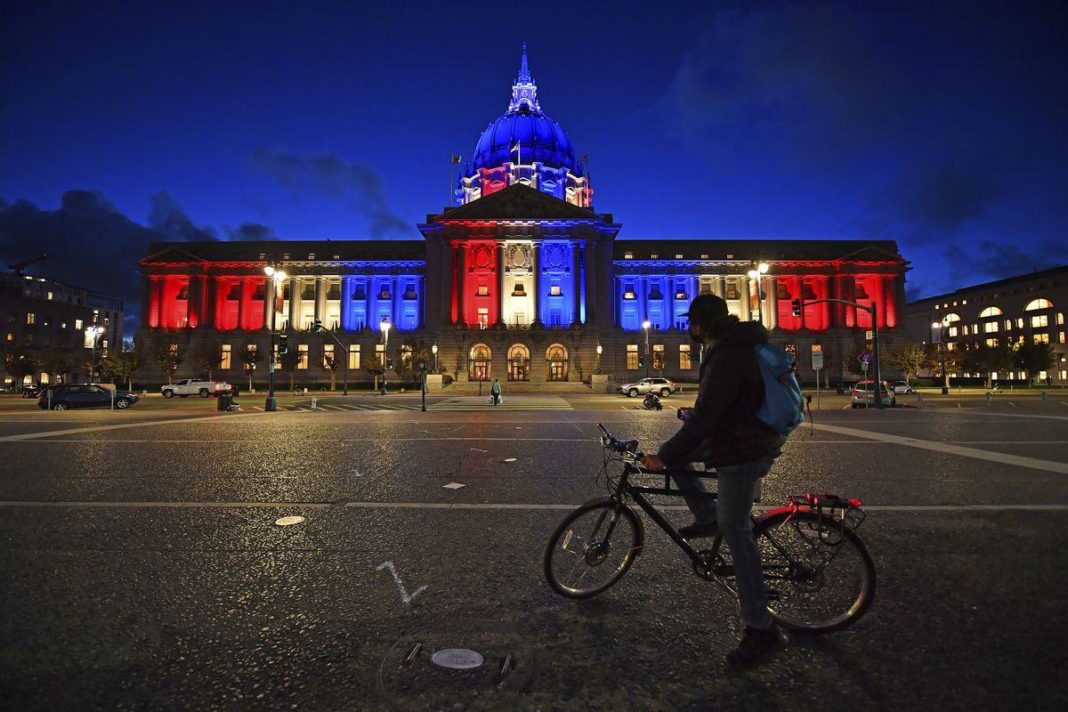 A bicyclist stops to admire the red, white and blue lights illuminating San Francisco City Hall in San Francisco, Calif., Friday, Nov. 6, 2020.