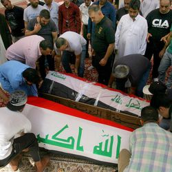 Mourners carry the Iraqi flag-draped coffins of bomb victims, Talib Hassan, 35, and Hamza Jabbar, 37, during their funeral processions at the holy shrine of Imam Ali in Najaf, 100 miles (160 kilometers) south of Baghdad, Iraq, Sunday, July 3, 2016. Dozens of people have been killed and more than 100 wounded in two separate bomb attacks in the Iraqi capital Sunday morning, Iraqi officials said.