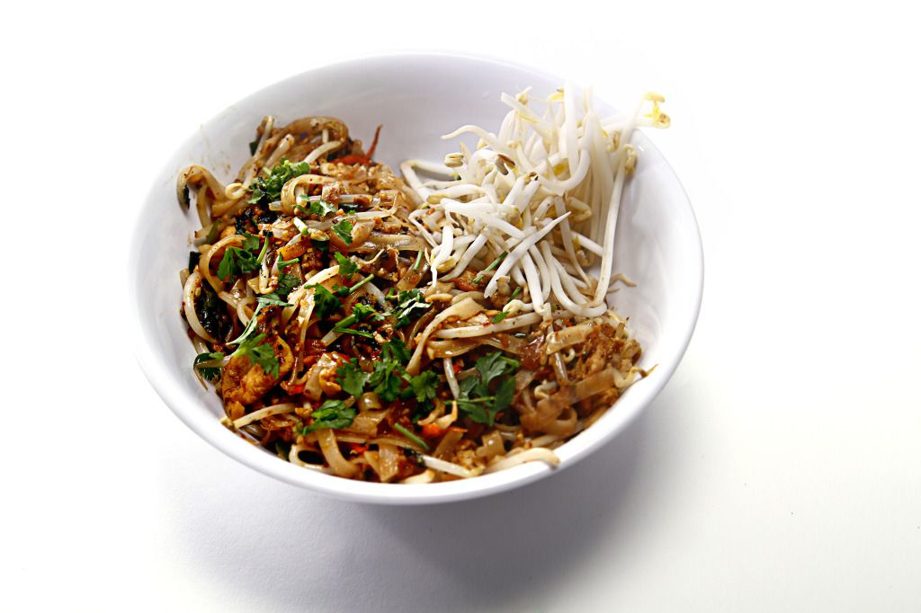 A bowl of pad Thai on a white surface