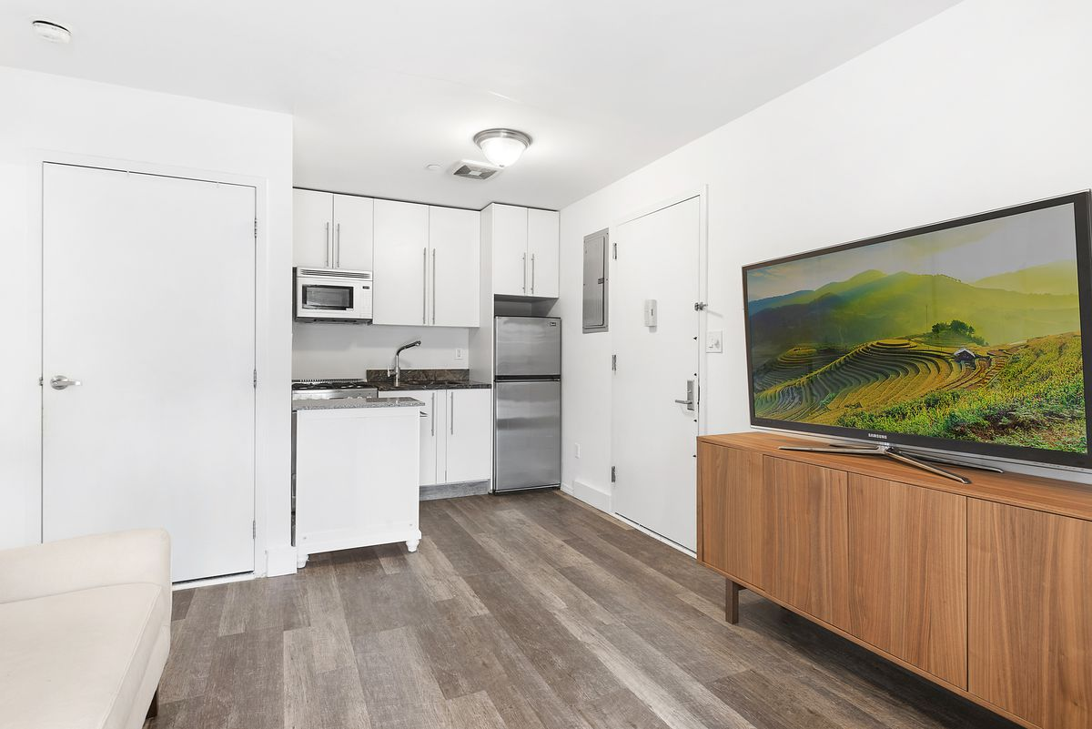 A living area with white walls, a large TV on a stand, and a small kitchen with white cabinetry in the back.