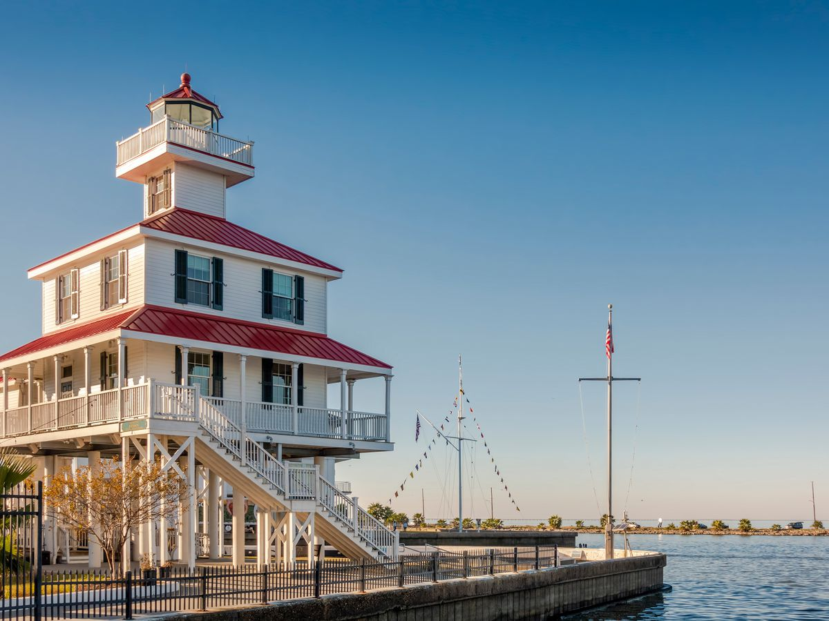 The exterior of the New Canal Lighthouse in New Orleans. The facade is white with multiple red roofs. The lighthouse is adjacent to a body of water.