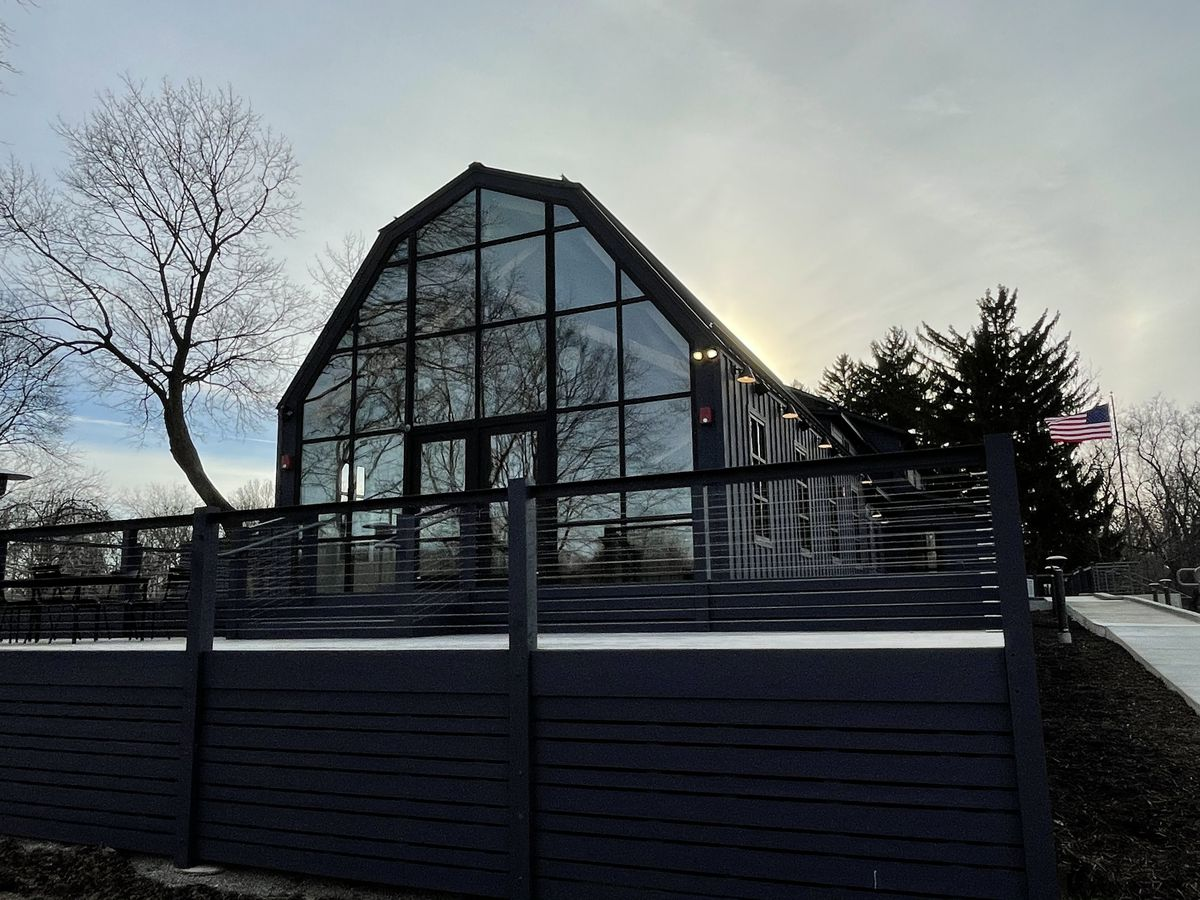 A shot at dusk of the floor-to-ceiling glass windows of the old barn now home to Dixboro House in Ann Arbor. An American flag flies straight on the right of the building