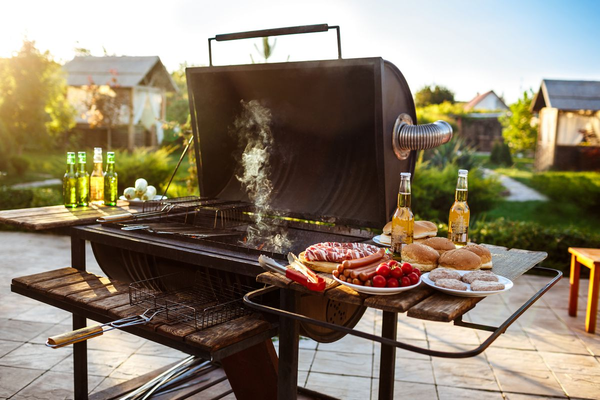 Open grill with smoke rising from it and food setting on the right shelf.