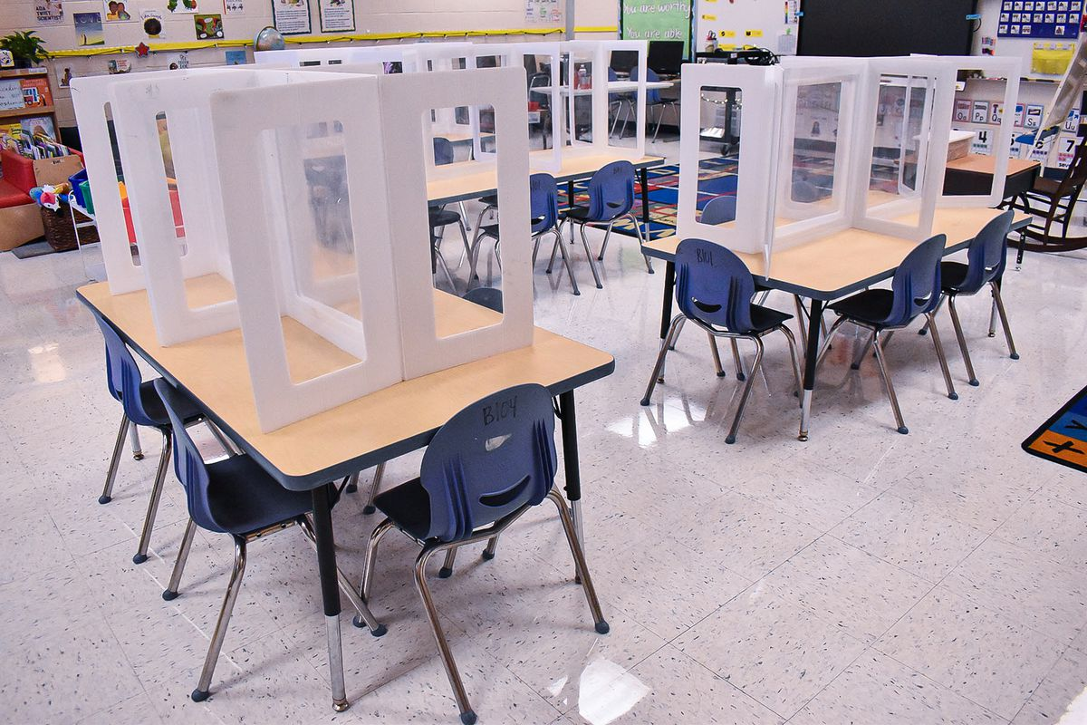 Desks in a classroom are lined with glass partitions to prevent the spread of COVID.