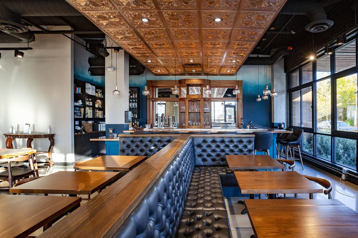 A wide angle shot of Communion's dining room, with dark navy booths a copper-toned roof, tables, and a bar in the back.