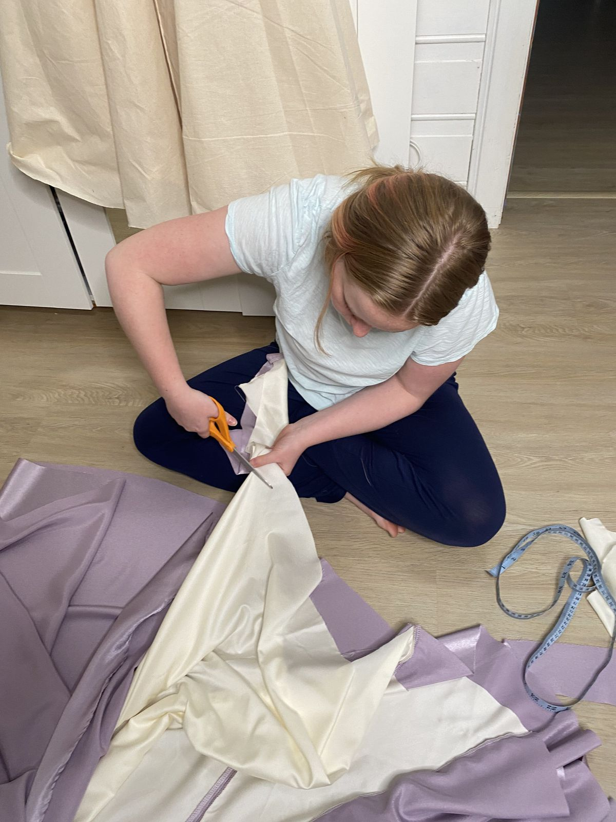 A teenager sits on her floor cutting fabric.