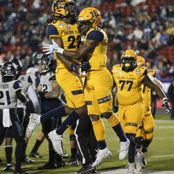 Kent State running back Xavier Williams (18) is congratulated by wide receiver Isaiah McKoy (23) after scoring a touchdown against Utah State during the first half of the Frisco Bowl NCAA college football game Friday, Dec. 20, 2019, in Frisco, Texas.
