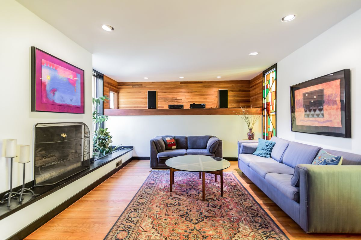 A living room with a fireplace to the left, hardwood floors, and a built-in display wall.