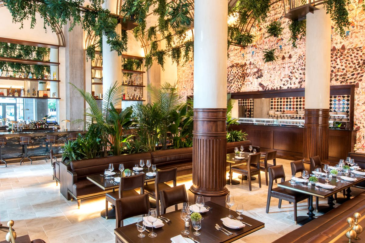 A restaurant interior featuring high ceilings, elegant columns, and lots of greenery