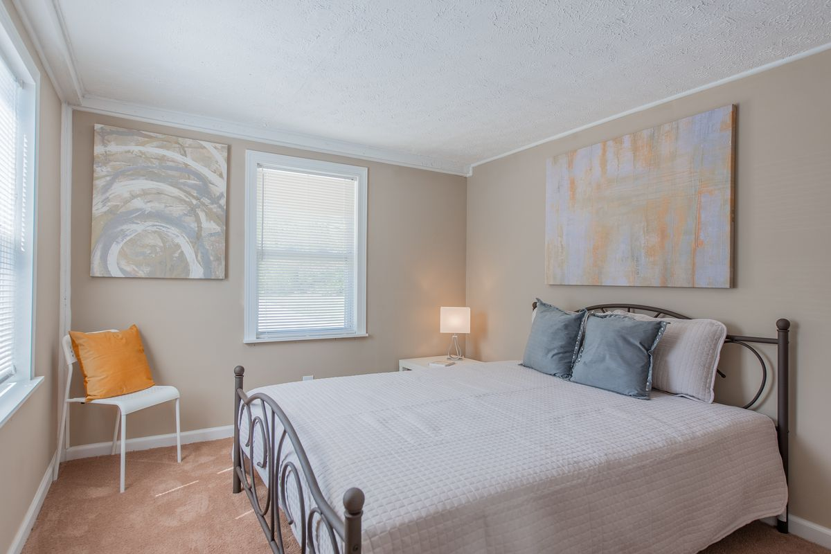 A bedroom with a bed covered in white sheets and a series of abstract painting hanging on the wall.