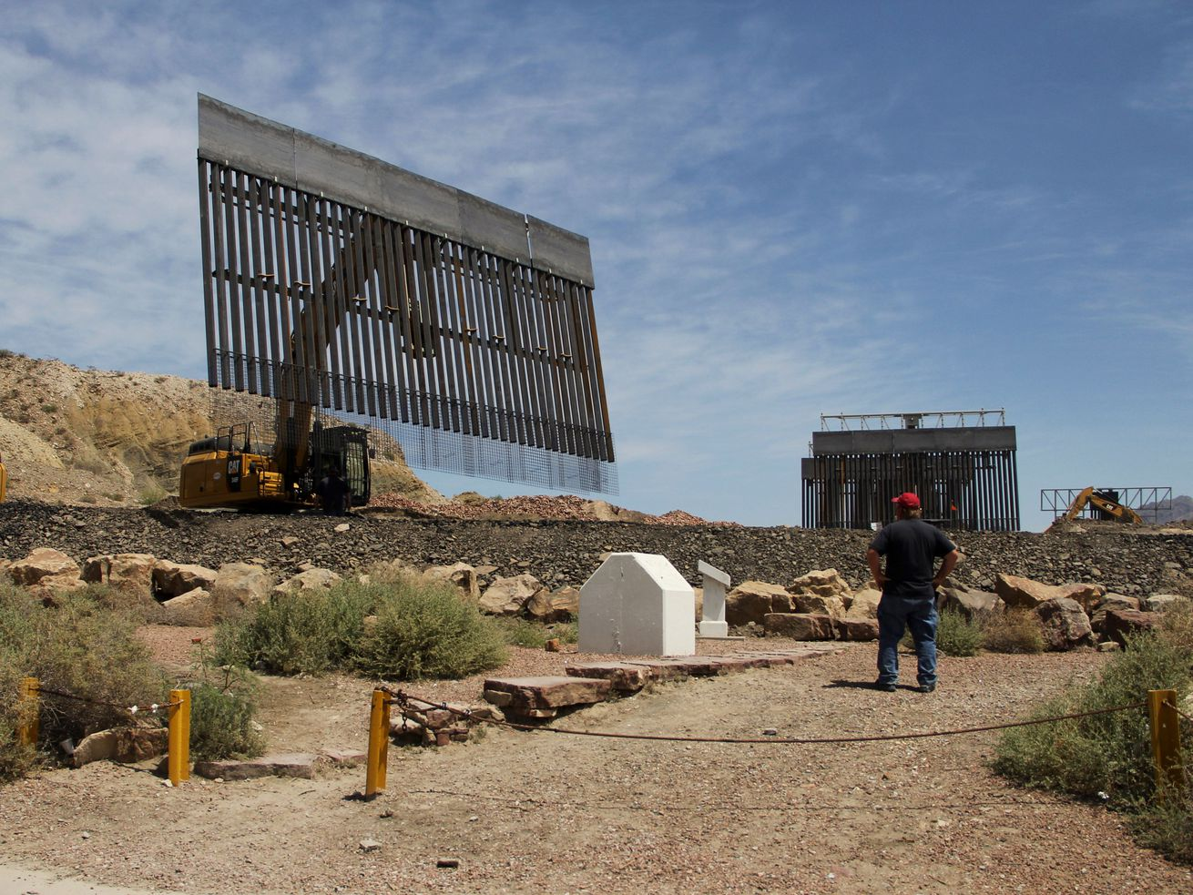 Cranes lift sections of border wall as a man in a red cap looks on.