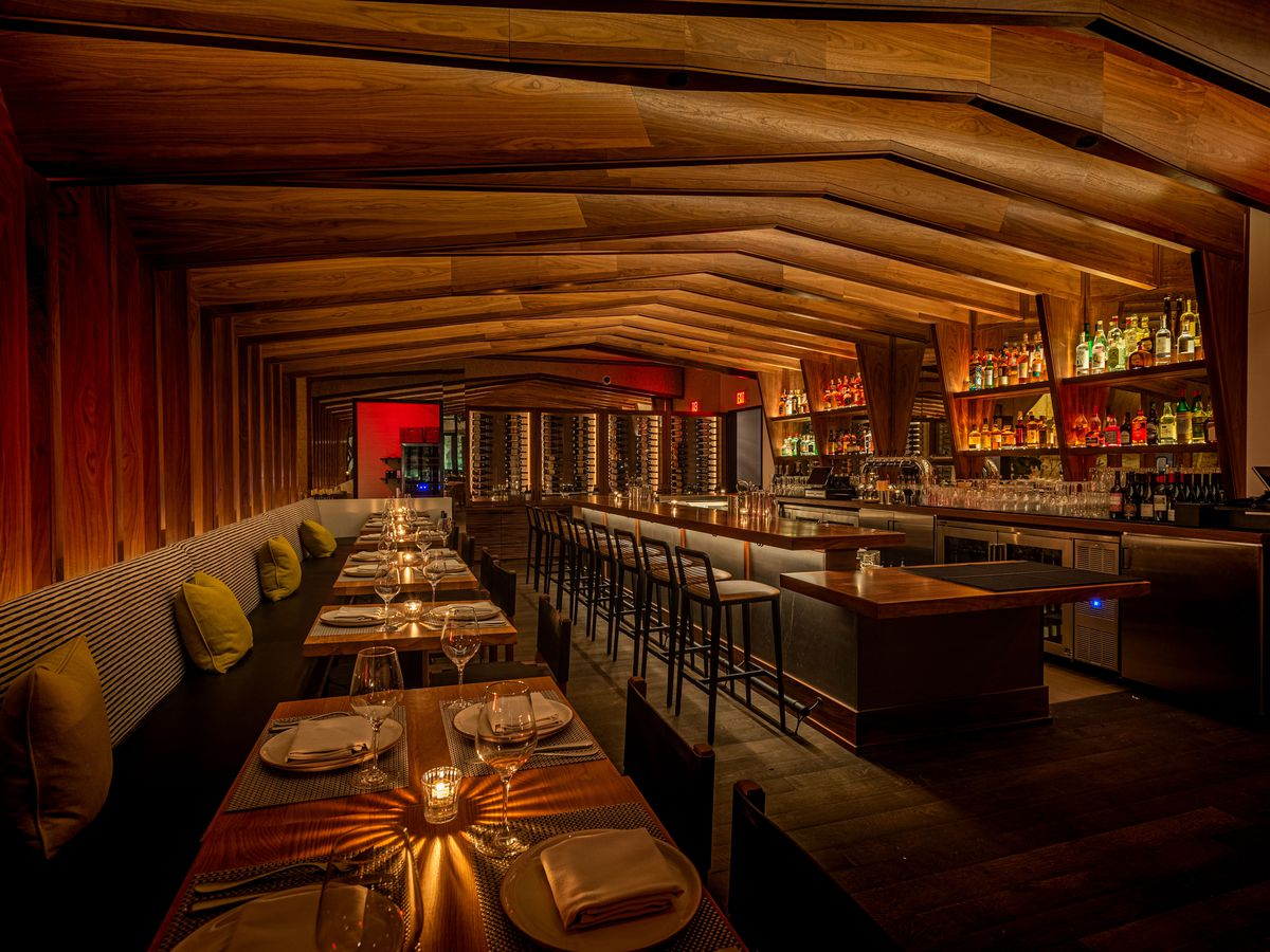 A pitched roof inside of a dark restaurant at night with pitched wooden beams.