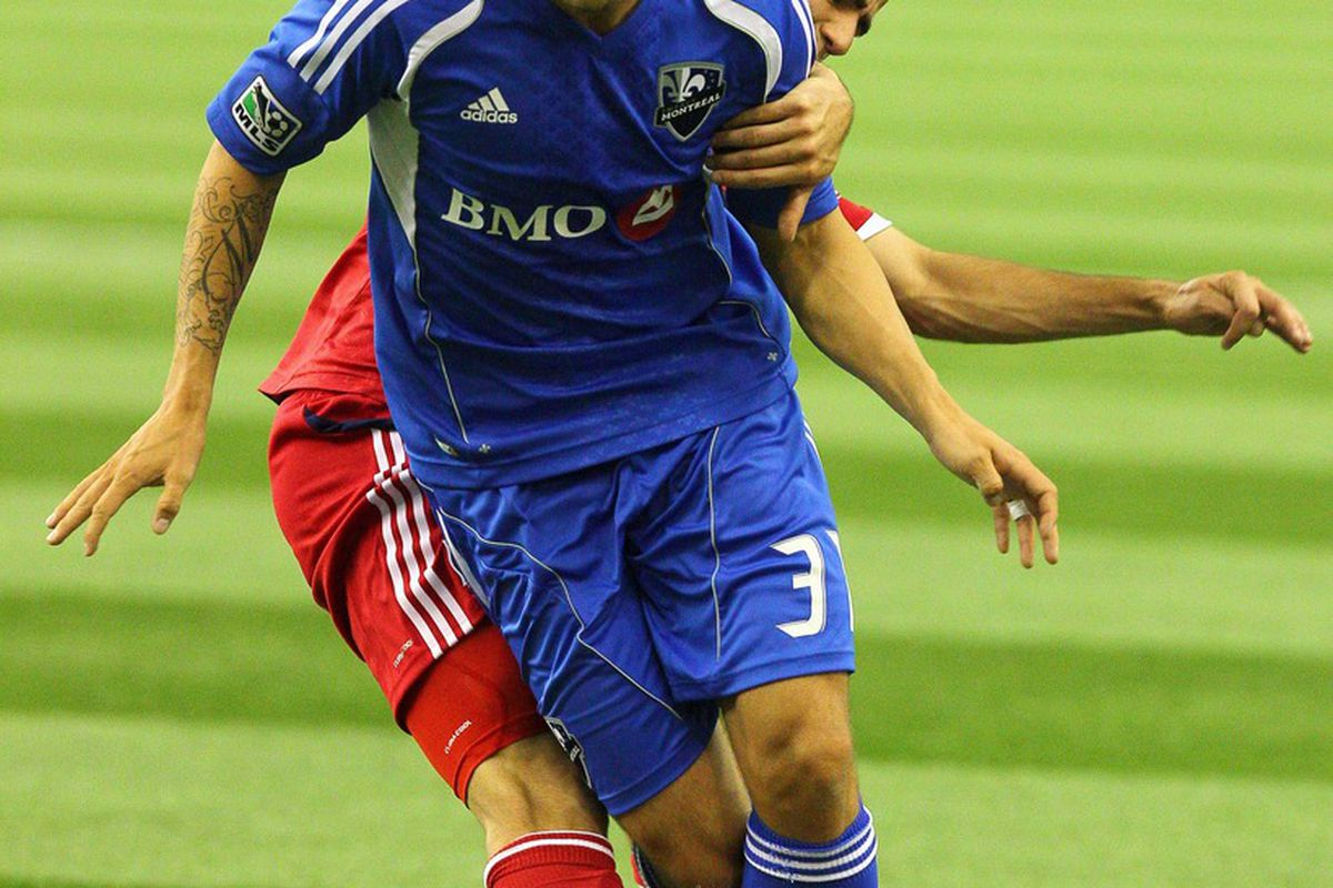 March 17, 2012; Montreal, QC, CAN; Chicago Fire forward Patrick Nyarko (14) and Montreal Impact defenseman Josh Gardner (31) battle for the ball during the first half at the Olympic Stadium. Mandatory Credit: Jean-Yves Ahern-US PRESSWIRE.