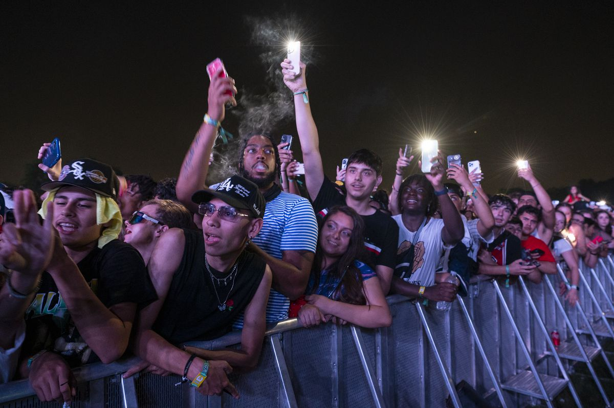 Festivalgoers hold their phones up in the air as Lil Baby performs.