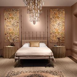Kara Mann of Kara Mann Design created the bedroom. Elements include a chandelier, a smoky-brass and sheepskin stool, and an Italian iron bed.