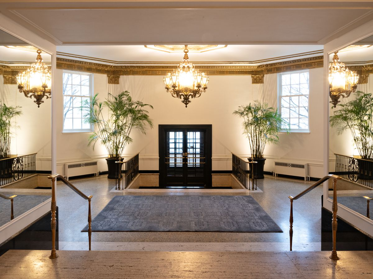 A grand entryway with marble floors and an elegant chandelier