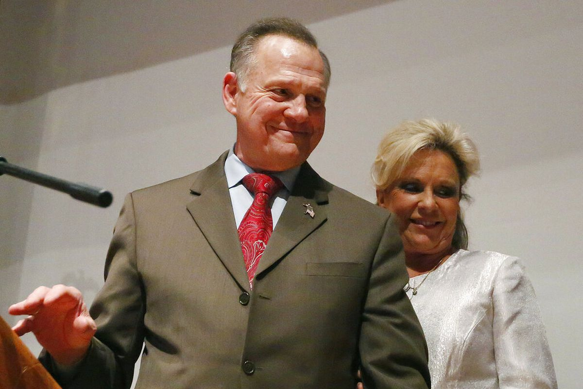 Roy Moore walks off a stage with wife Kayla Moore