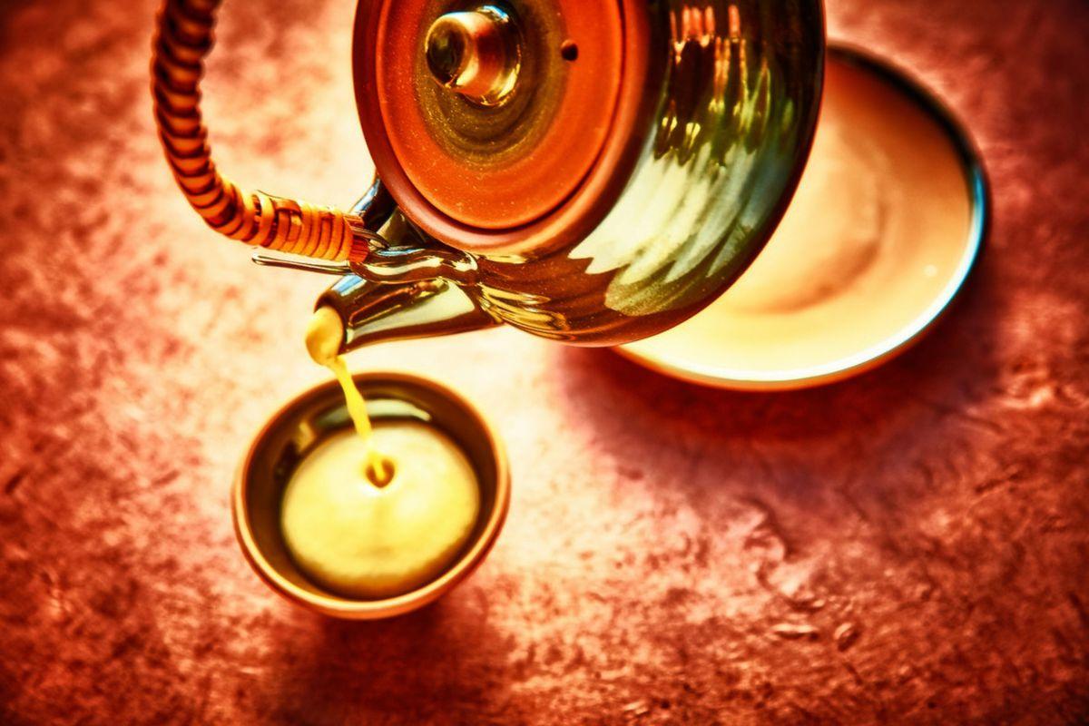 A tea kettle pouring soup into a round tea cup.