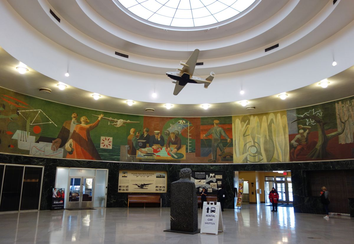 An airport terminal. The terminal is circular shaped and has multiple colorful murals depicting people doing various actions. There is a small model airplane hanging from a skylight.