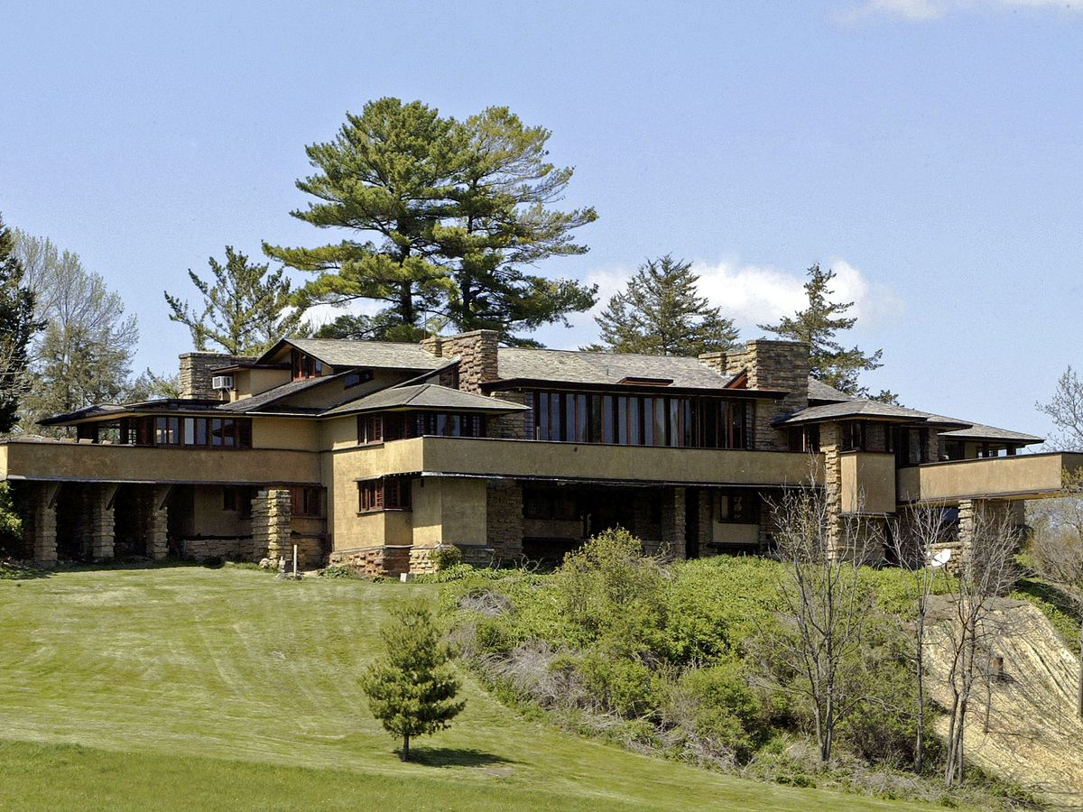 Taliesin by Frank Lloyd Wright. The facade is tan with a dark brown roof. There is a green lawn in front of the house.
