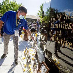 Scott Mitchell places a yellow rose in memory of his son, Staff Sgt. Alex Scott Mitchell, U.S. Air Force, at the base of the new Gold Star Families Memorial Monument in North Ogden on Saturday, Aug. 1, 2020.
