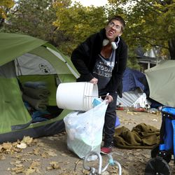 Tasha cleans up the garbage surrounding her tent before being evicted from Taufer Park in Salt Lake City on Friday, Oct. 23, 2020. Tasha was unsure as to where she would go but was thinking about setting up camp on Rio Grande Street outside the now-shuttered Road Home shelter downtown.