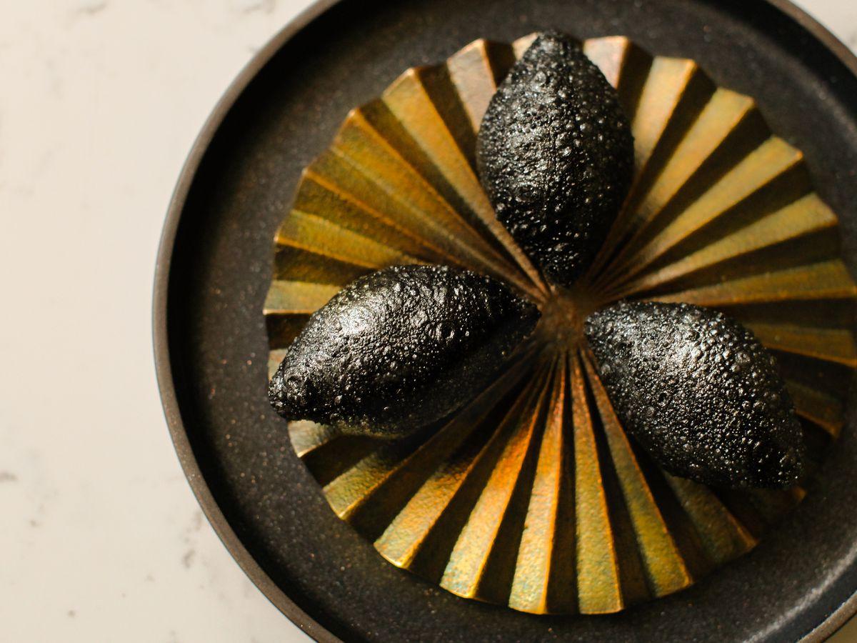 Three black oblong dumplings arranged on a golden ridged platter sitting on a black plate on a white background.