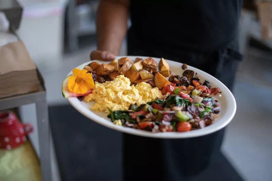 A hand holds a plate of potatoes, eggs, and sauteed vegetables from Po'Shines