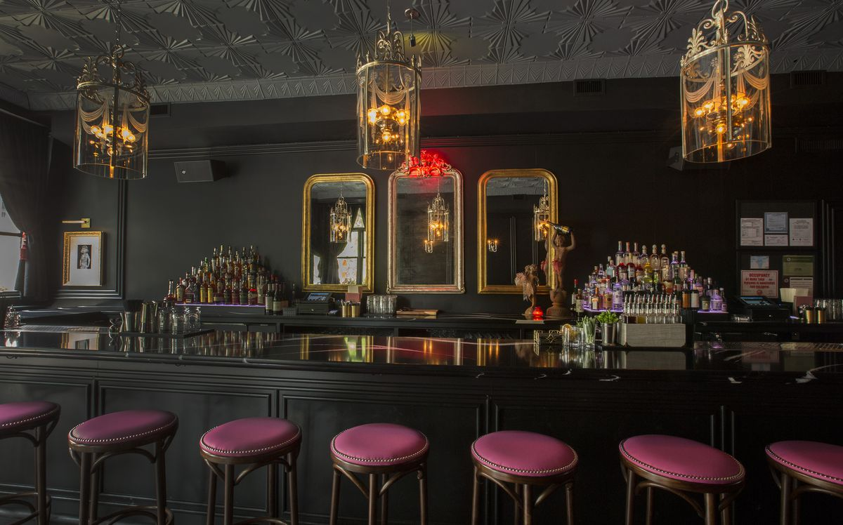 A black bar with glass top, pink stools with vintage lights and mirrors.