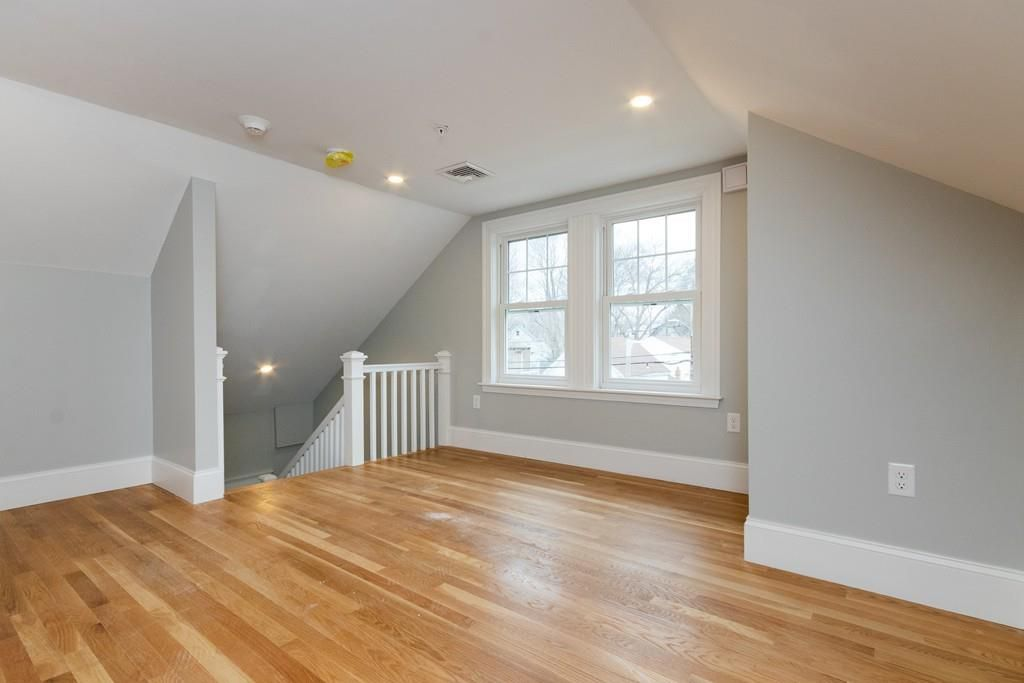An empty, open room with a stairwell leading down from it.