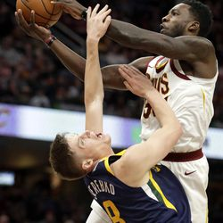 Cleveland Cavaliers' Jeff Green, top, fouls Utah Jazz's Jonas Jerebko (8), from Sweden, in the second half of an NBA basketball game, Saturday, Dec. 16, 2017, in Cleveland. (AP Photo/Tony Dejak)