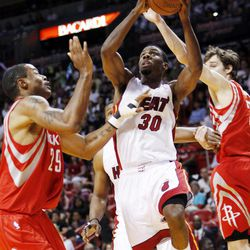 Miami Heat guard Norris Cole (30) shoots against Houston Rockets center Marcus Camby (29) and guard Goran Dragic during the first half of an NBA basketball game, Sunday, April 22, 2012, in Miami.