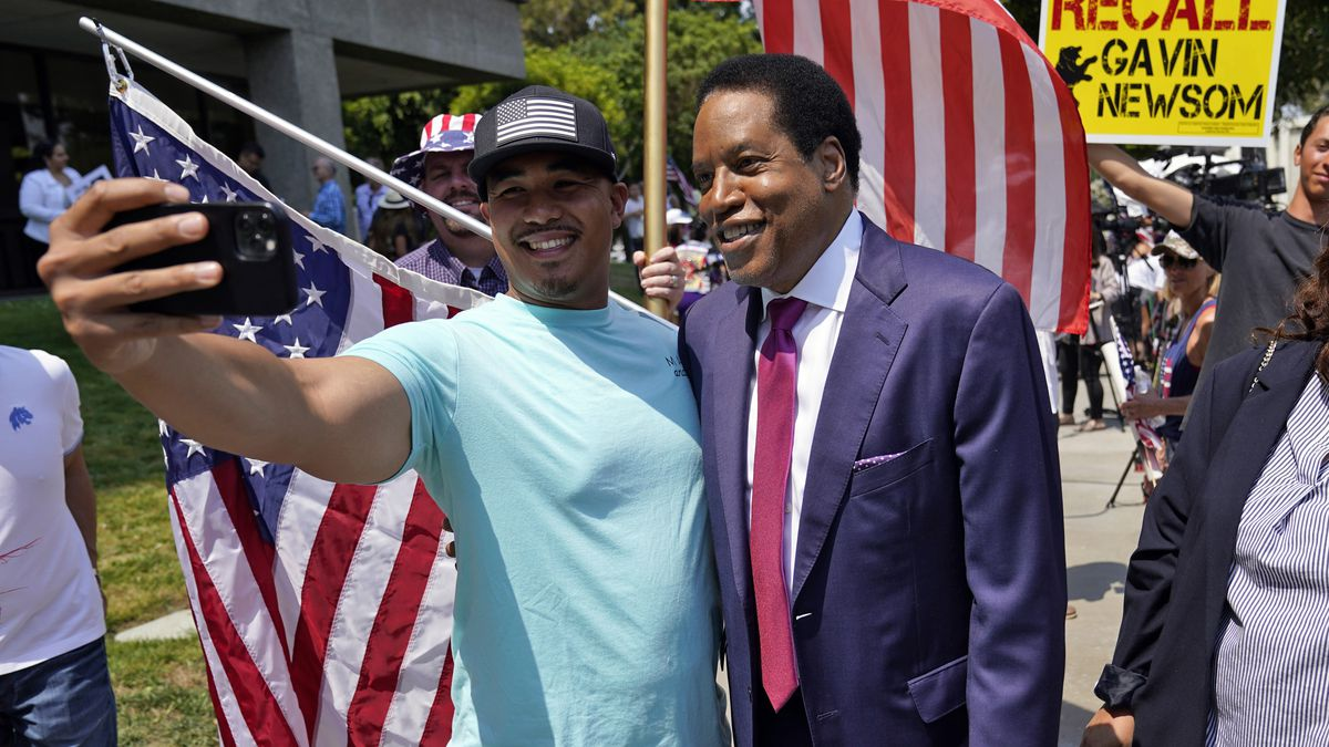Radio talk show host Larry Elder poses for a selfie with a supporter during a campaign stop in Norwalk, Calif.