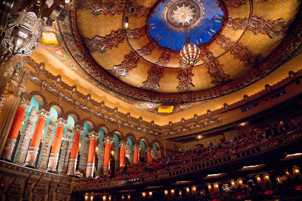 The interior of the Fox Theatre in Detroit. The ceiling and walls are elaborately decorated. There are colorful columns and hanging chandeliers. There are many rows of seats on a balcony level.