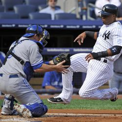 New York Yankees' Robinson Cano, right, scores on a sacrifice fly by Curtis Granderson as Toronto Blue Jays catcher Jeff Mathis fields the throw during the first inning of the first baseball game of a doubleheader, Wednesday, Sept. 19, 2012, at Yankee Stadium in New York.