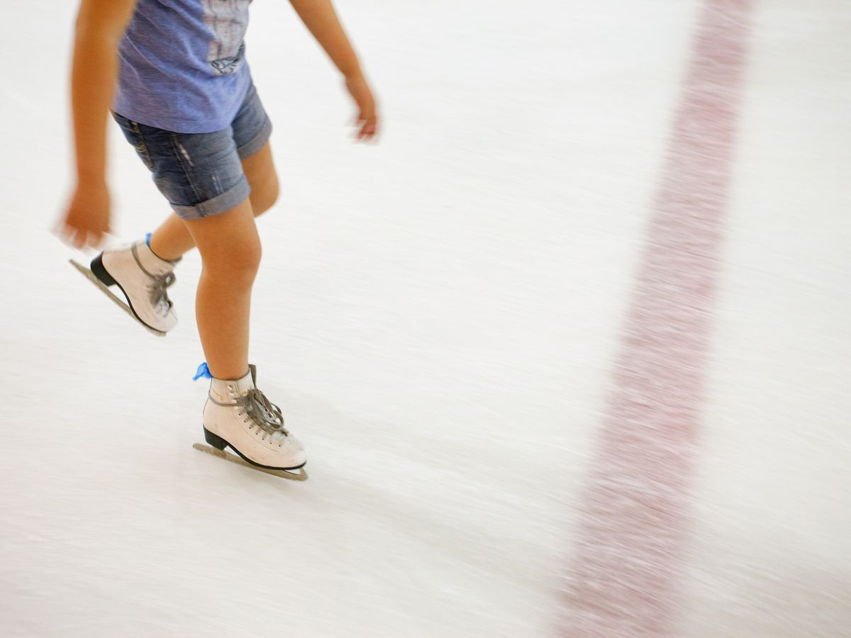 A child is seen skating on an ice rink from the waist down.